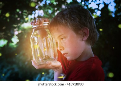 Boy looking into a jar of fireflies