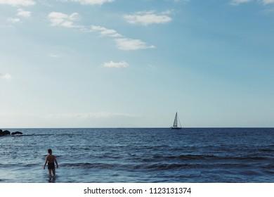 Boy looking on yacht on the sea