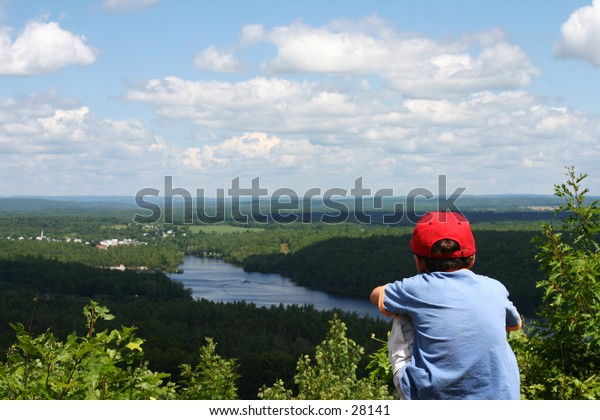 Boy looking out across a river