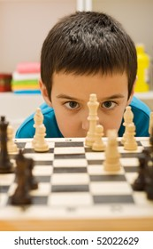 Boy looking at piece of chess