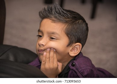 boy looking to right side, hand on cheek