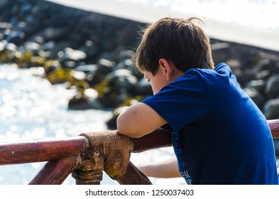 A boy looking at the sea with his back to the camera. Child looking at the sea on the beach