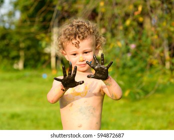 Boy looking skeptically on his black palms painted with oil paint