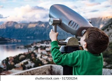 Boy looking through binocular at the city of Kotor, Montenegro