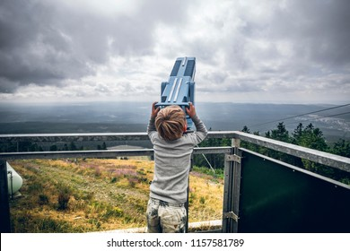 Boy looking through binoculars at a lookout point in cloudy weather