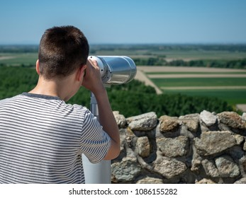 Boy looking through binoculars and observe nature.