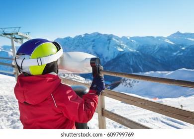 Boy looking through binoculars on mountain scenes