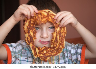 Boy is looking through the hole of pancake