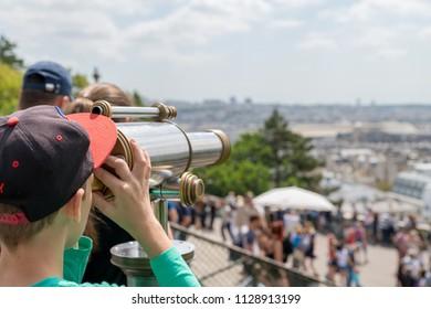 Boy looking through an observation telescope at Paris  city skyline