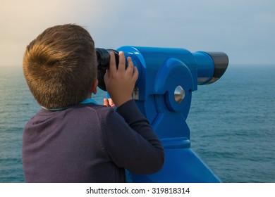 A boy looking through sightseeing binoculars tourist telescope overlooking the ocean landscape