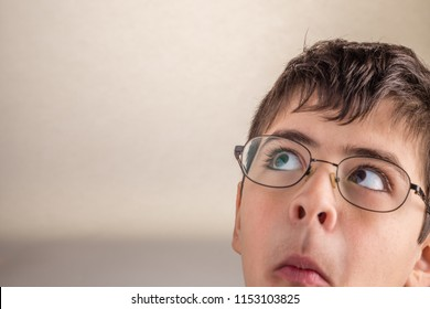 Boy looking upwards at his side sucks cheeks and  squeezes his lips making weird face as a sign of surprise