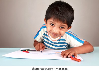 A boy looking while painting on a white paper