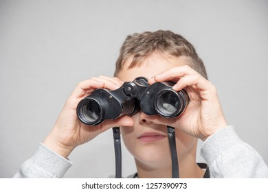 Boy looks with black binoculars into the future with white background