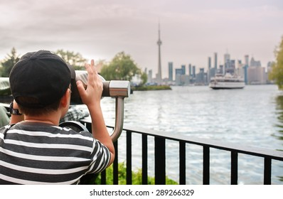The boy looks at the city through a telescope