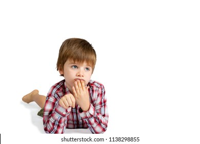 A boy looks deep in thought, laying on his stomach with his hand to his lips.  His fingernails are dirty and he looks confused. Isolated on white with clipping path.