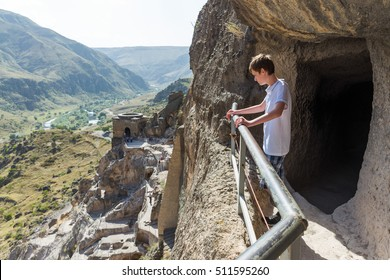 Boy looks down on Vardzia. It is a medieval cave town situated on the left bank of the Mtkvari River, near Akhaltsikhe, Georgia.