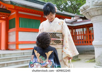 A boy looks up at his proud and happy mother at a Japanese shrine for the 7-5-3 Ceremony, a rite of passage for children each November 15; both are dressed in elegant kimonos