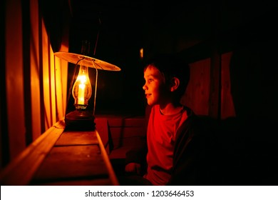 boy looks at an old lamp. the child at the dark with a burning candle