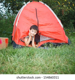 boy looks out from a tent