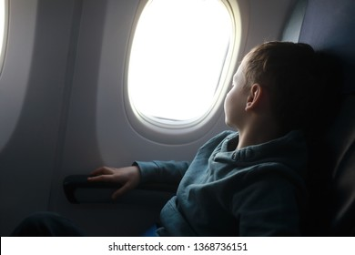 Boy looks out window of the plane