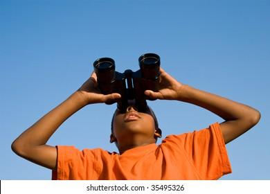 a boy looks skywards through binoculars