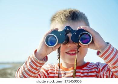boy looks through binoculars and sees sea