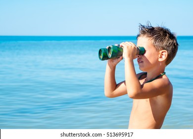 boy looks through binoculars and sees sea