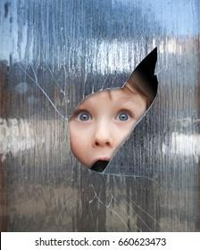 boy looks through a broken window