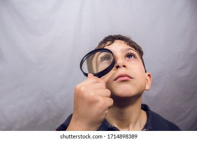 boy looks through a magnifier on a gray background