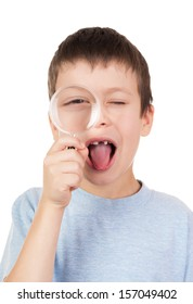 boy looks through a magnifying glass