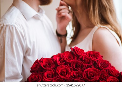 boy in love gives a girl a big bouquet of roses, Valentine's Day, marriage proposal