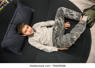 boy lying in the big round black sofa with pillow under his head, watching and smiling