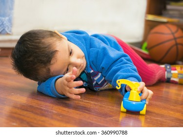 boy lying down playing with toy car