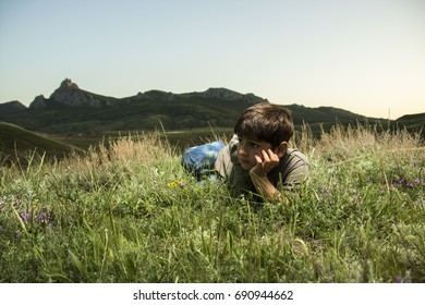 Boy lying in grass at backdrop of the mountains