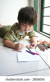 Boy lying on the floor and drawing on the paper