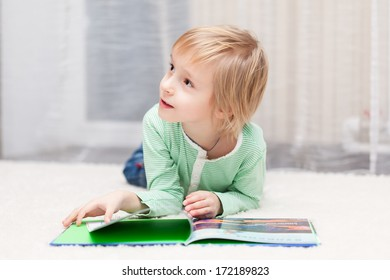Boy is lying on the floor and reading book