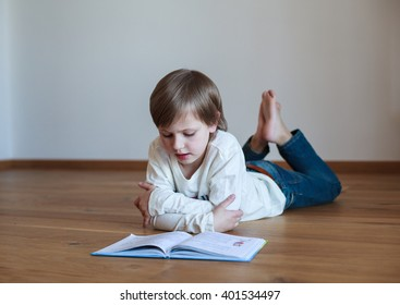 boy lying on the floor and reading book