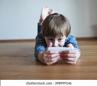 boy lying on the floor and using mobile phone