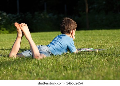 A boy lying on the grass reading a newspaper