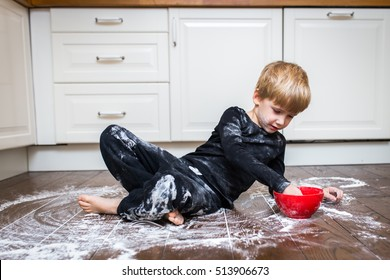 Captivating A Boy Lying On The Kitchen Floor And Playing With Flour.