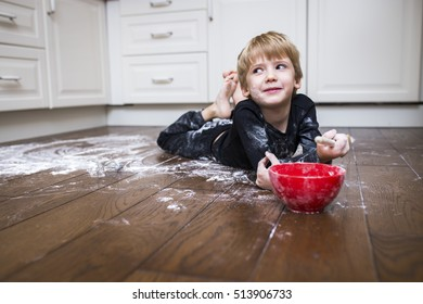 A boy lying on the kitchen floor and playing with flour.