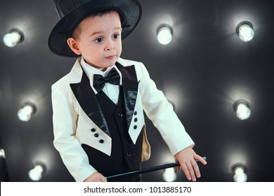 A boy is a magician with a magic wand. The boy in a funny tuxedo