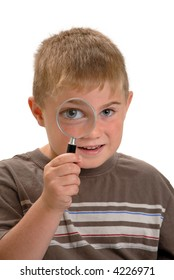 Boy with magnifying glass to his eye making eye bigger