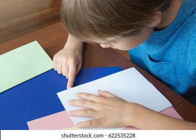 Boy makes greeting card using colored paper. Top view