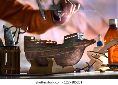 BOY MAKES A MODEL OF AN OLD SHIP FRIGATE MADE IN HANDS FROM THE CARDBOARD. NEAR GLUE, BRUSHES, SCISSORS AND STANGENCIRCLE