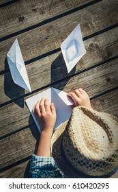 Boy makes paper boats - close up hands image