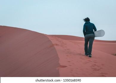 Boy makes sandboarding in the Sahara desert, Morocco. Safari desert camp in Merzouga