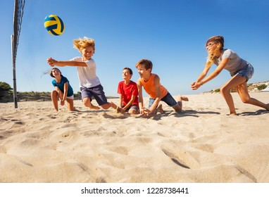 Boy making bump pass during beach volleyball game
