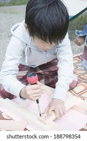 boy making handcrafts with wood outdoors