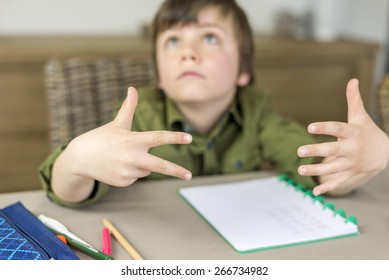 boy making homework, counting on his fingers. shallow depth of field